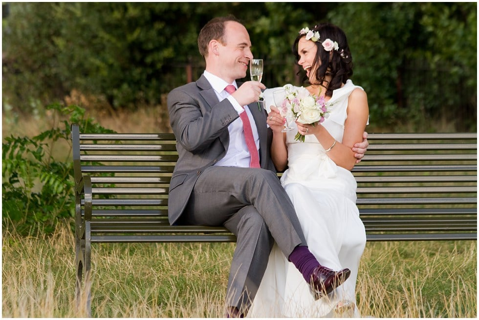 Laughing Bride and Groom very happy after being married at the Lido sat on Brockwell Park bench with champaigne
