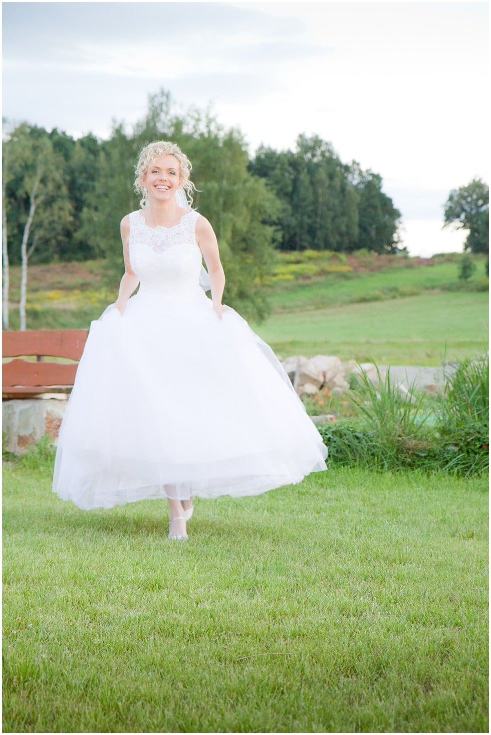 The bride running happily through a meadow and looking gorgeous at a wedding photographers dream wedding in Poland