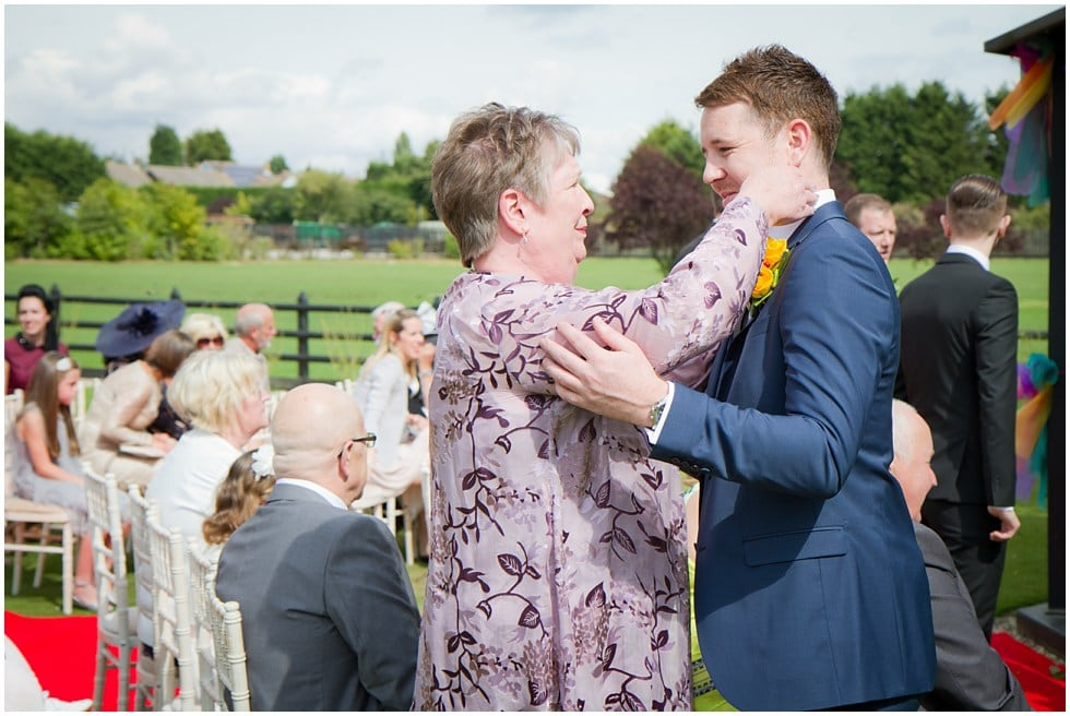 an emotional aunt squeezes the groom's cheeks