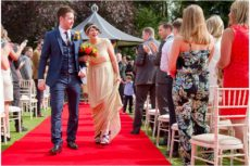 The Three Rivers Golf and Country Club Essex Wedding Photographer shot of bride and groom walking down the aisle of a beautiful outdoor wedding