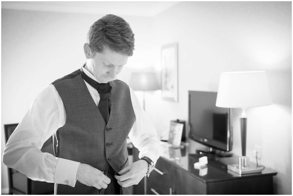 Groom doing up his waistcoat before his wedding