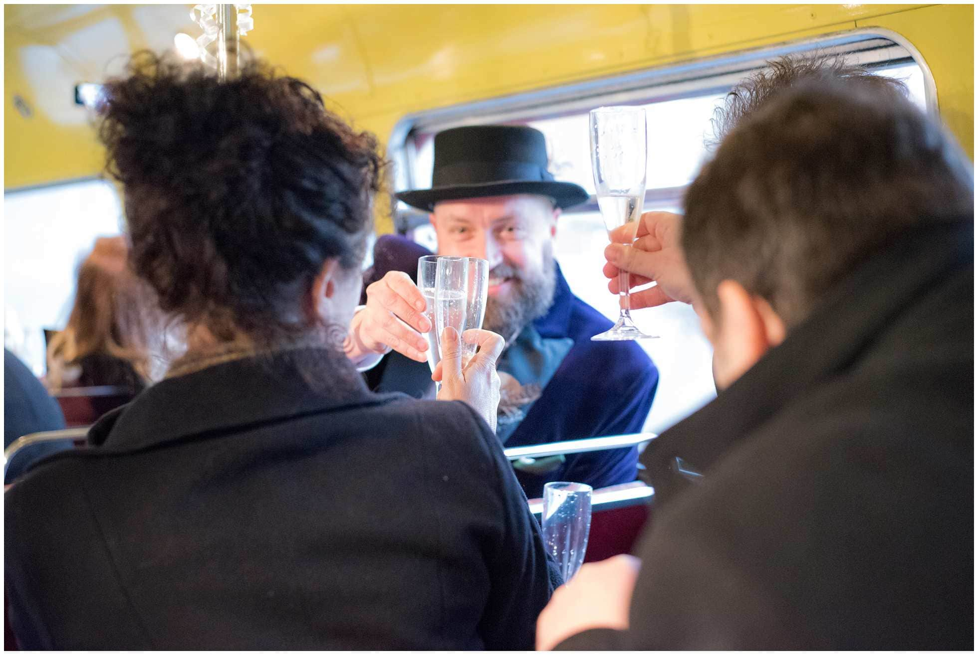 Grooms toasting on Routemaster bus london wedding photography