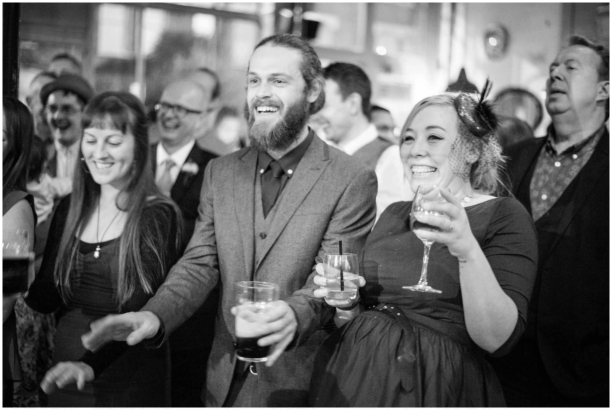 guests laughing at gay wedding reception