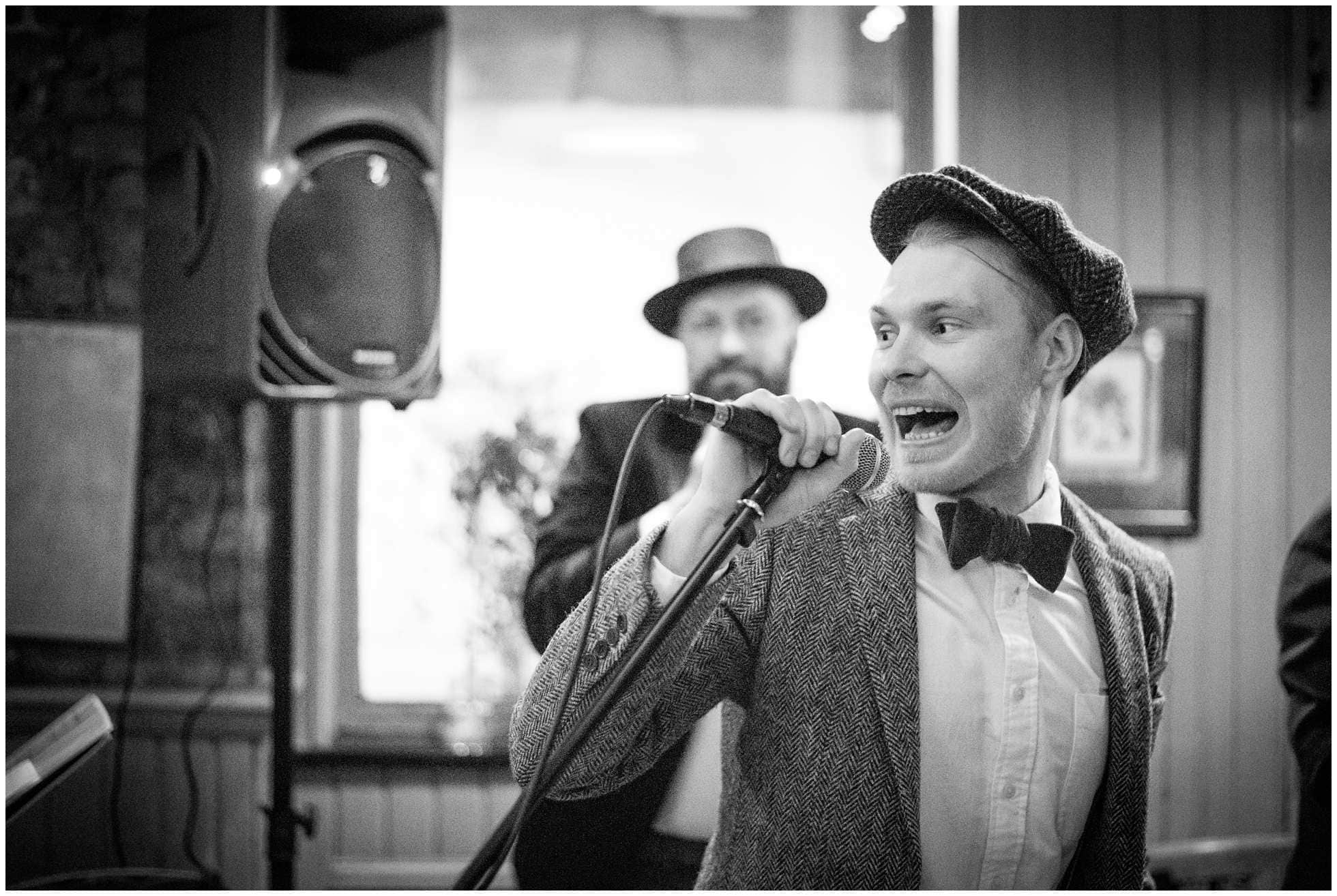 Groom rocking the microphone black and white classic london wedding photography