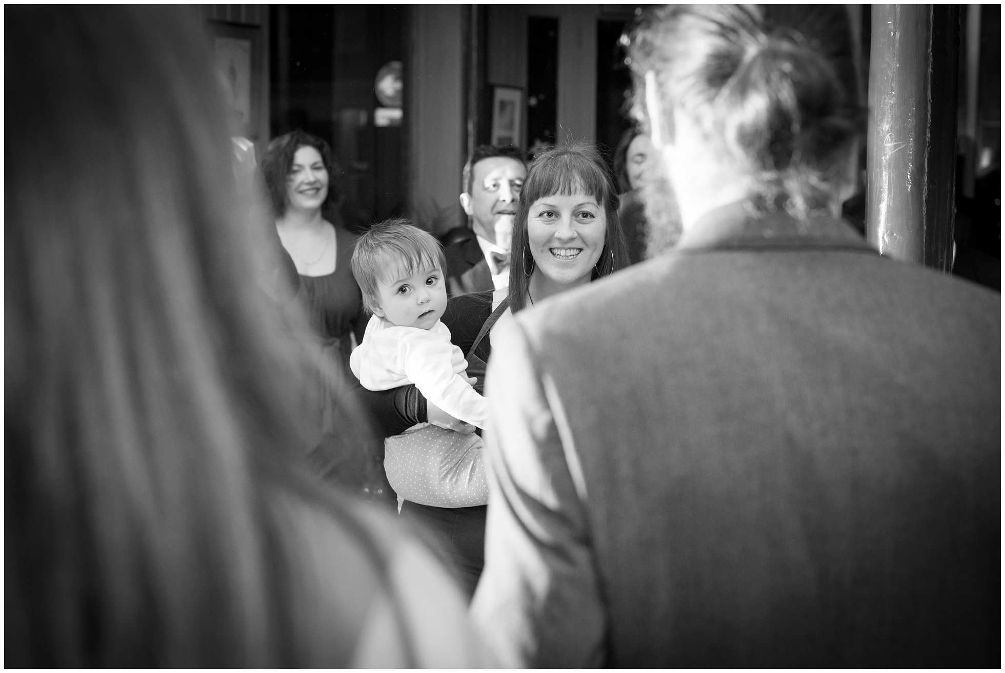 black and white shot of mum and baby at wedding near archway