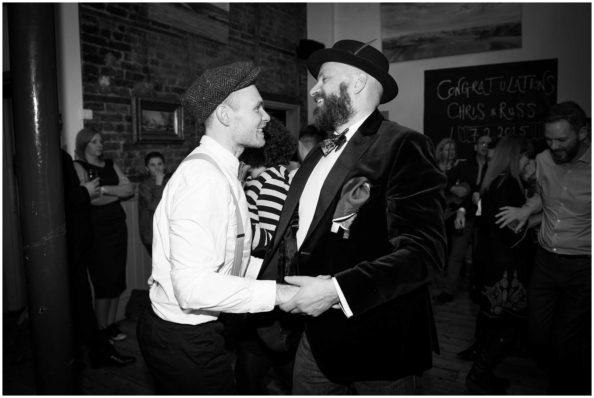 Two happy grooms ceilidh dancing in london