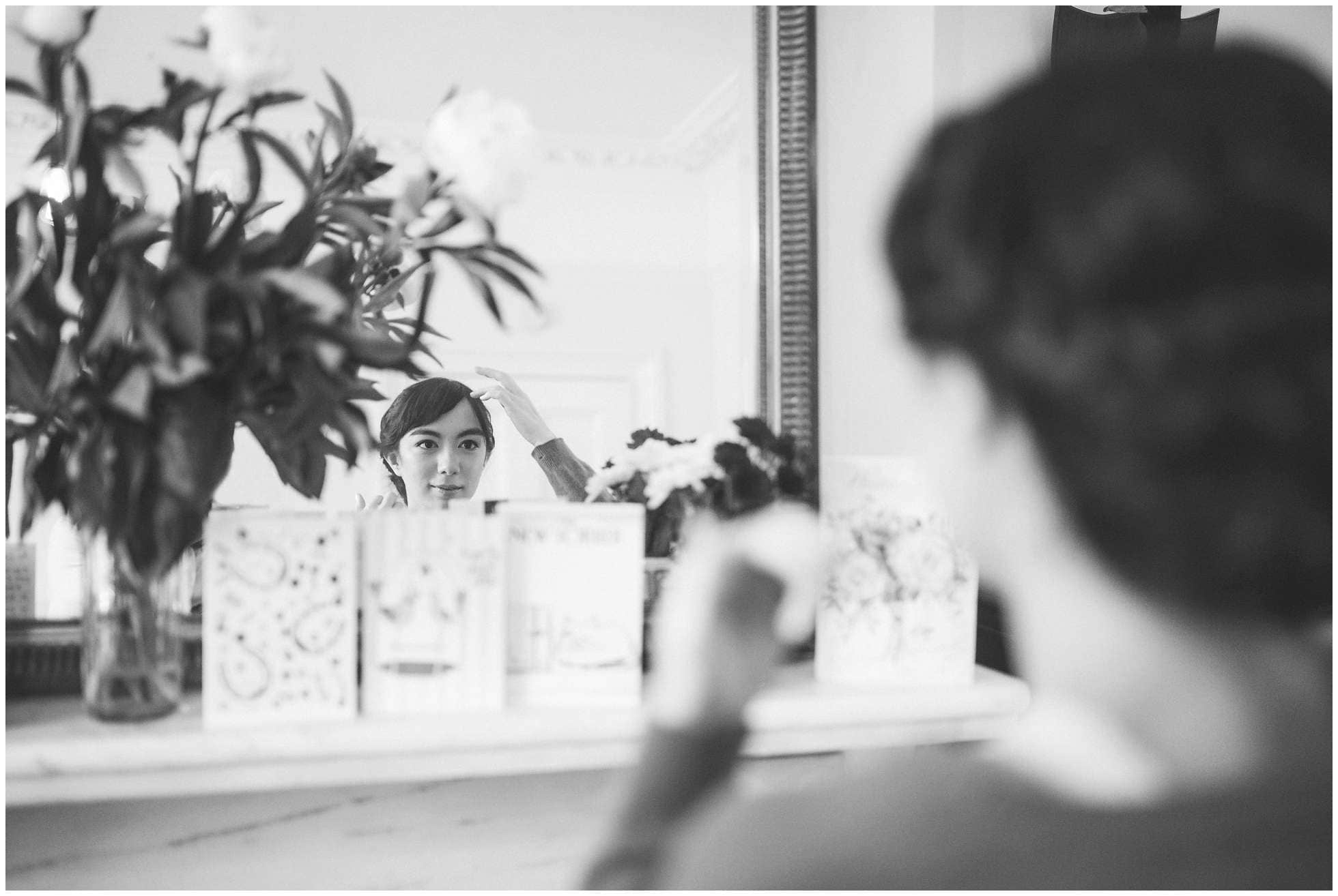 The London bride getting ready whilst looking in the mirror classic black and white wedding photography shot