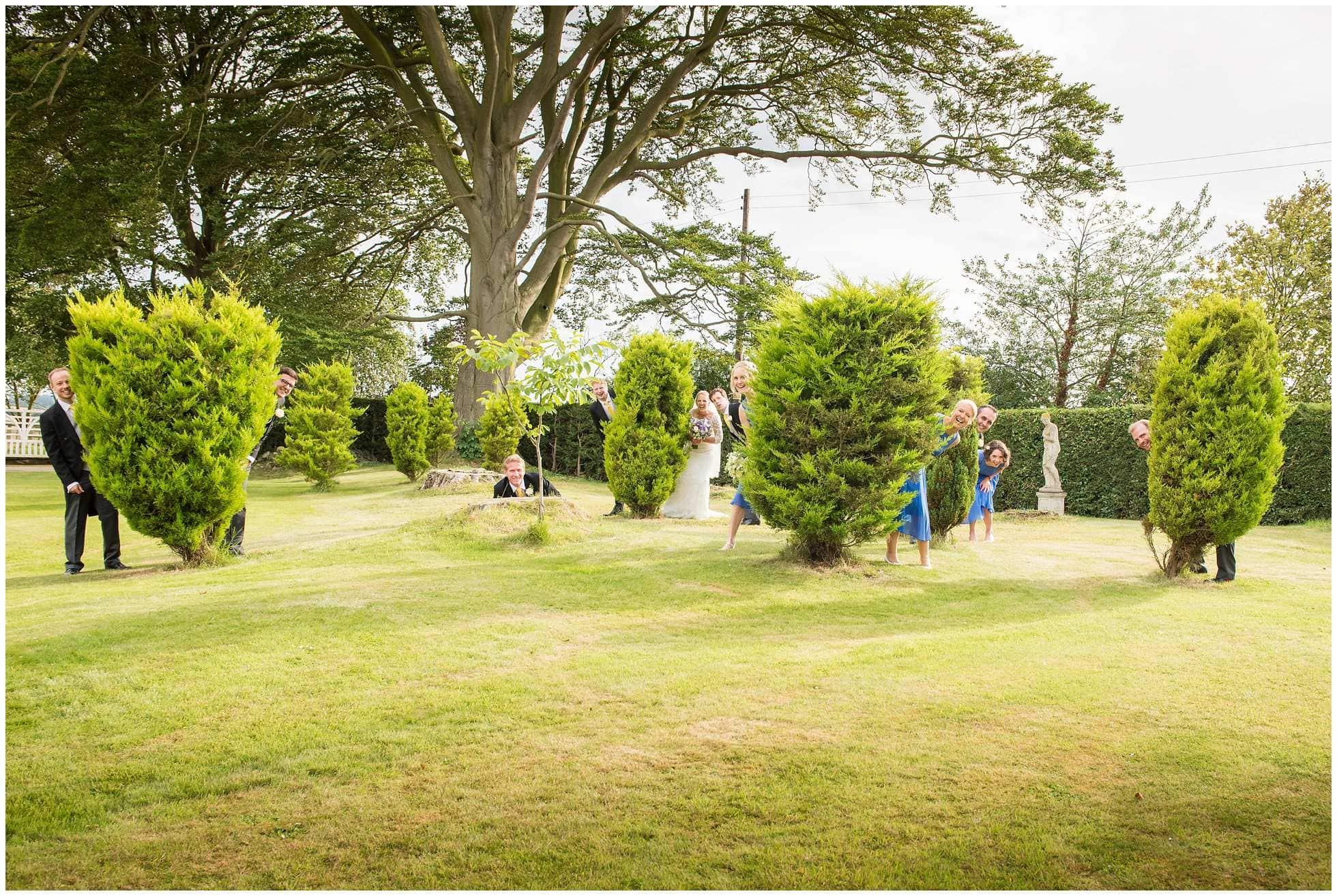Peeking from around bushes fun wedding portraits