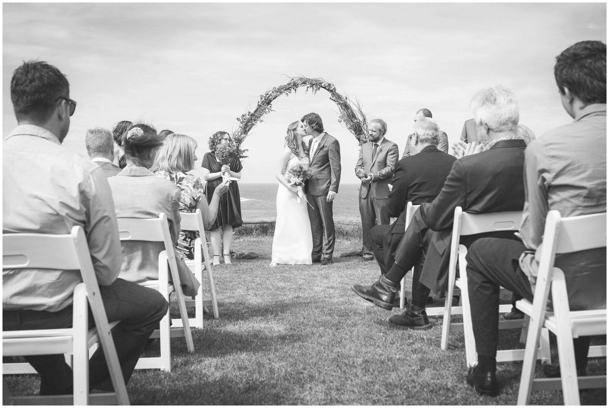 The bride and groom kiss at a wedding at the Robert Dun reserve