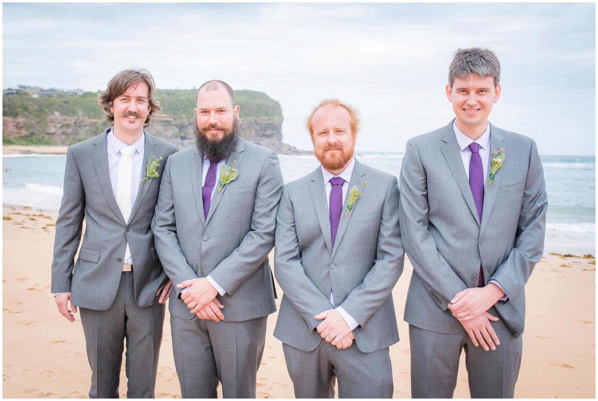 Groomsmen looking cool on the beach despite wearing warm suits