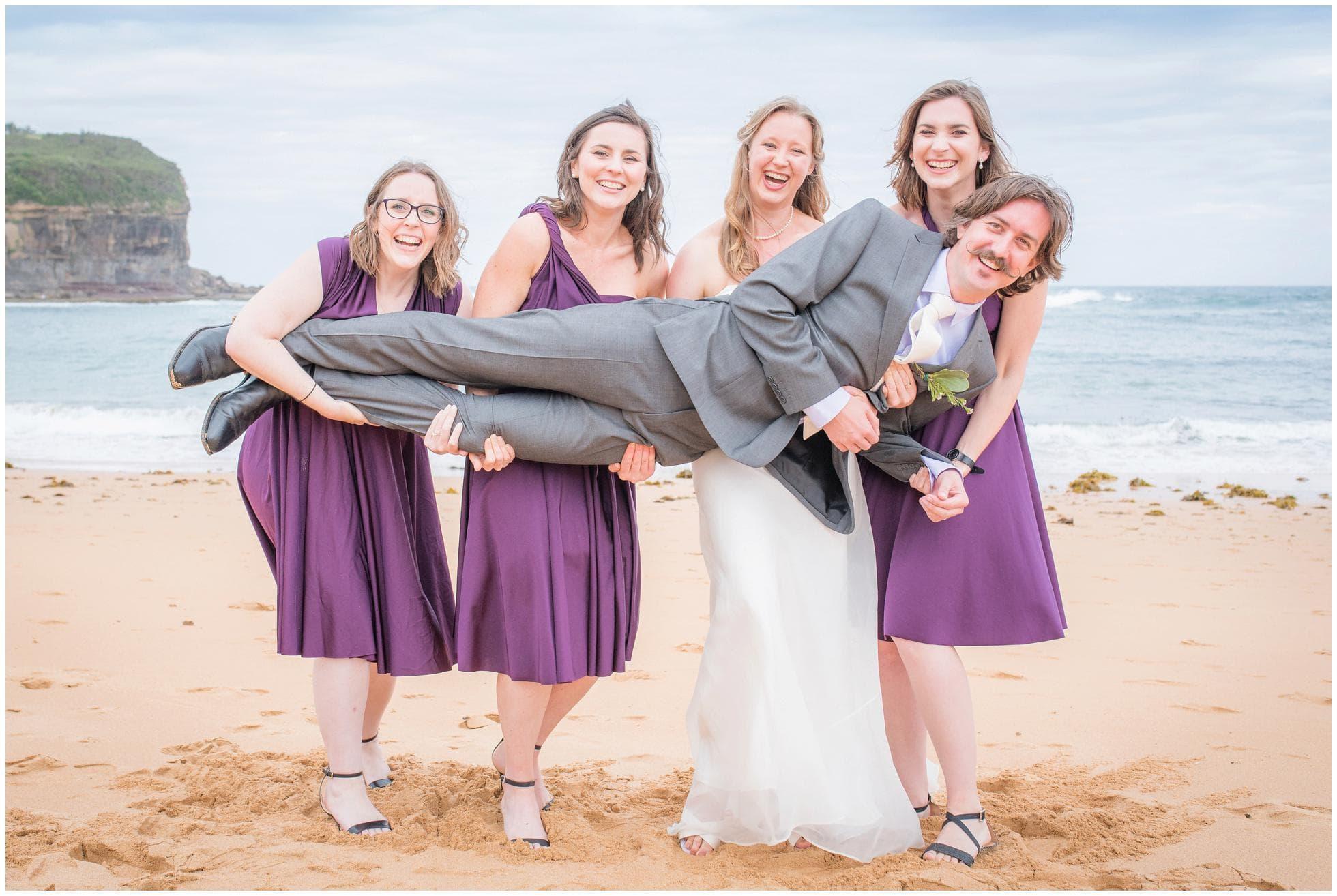 Bridesmaids holding up the groom on Mona Vale beach. Fun wedding photography!