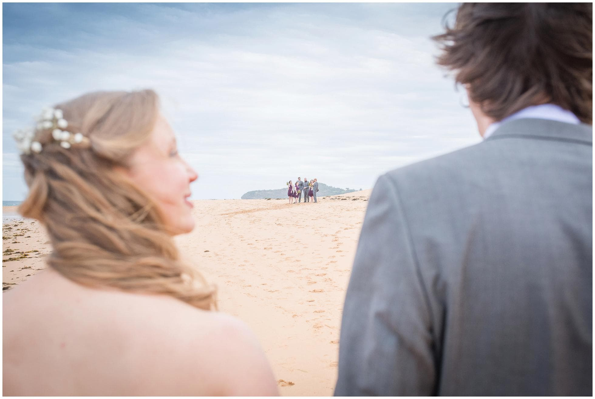 Bride and groom walking back to their bridal party on Mona Vale beach