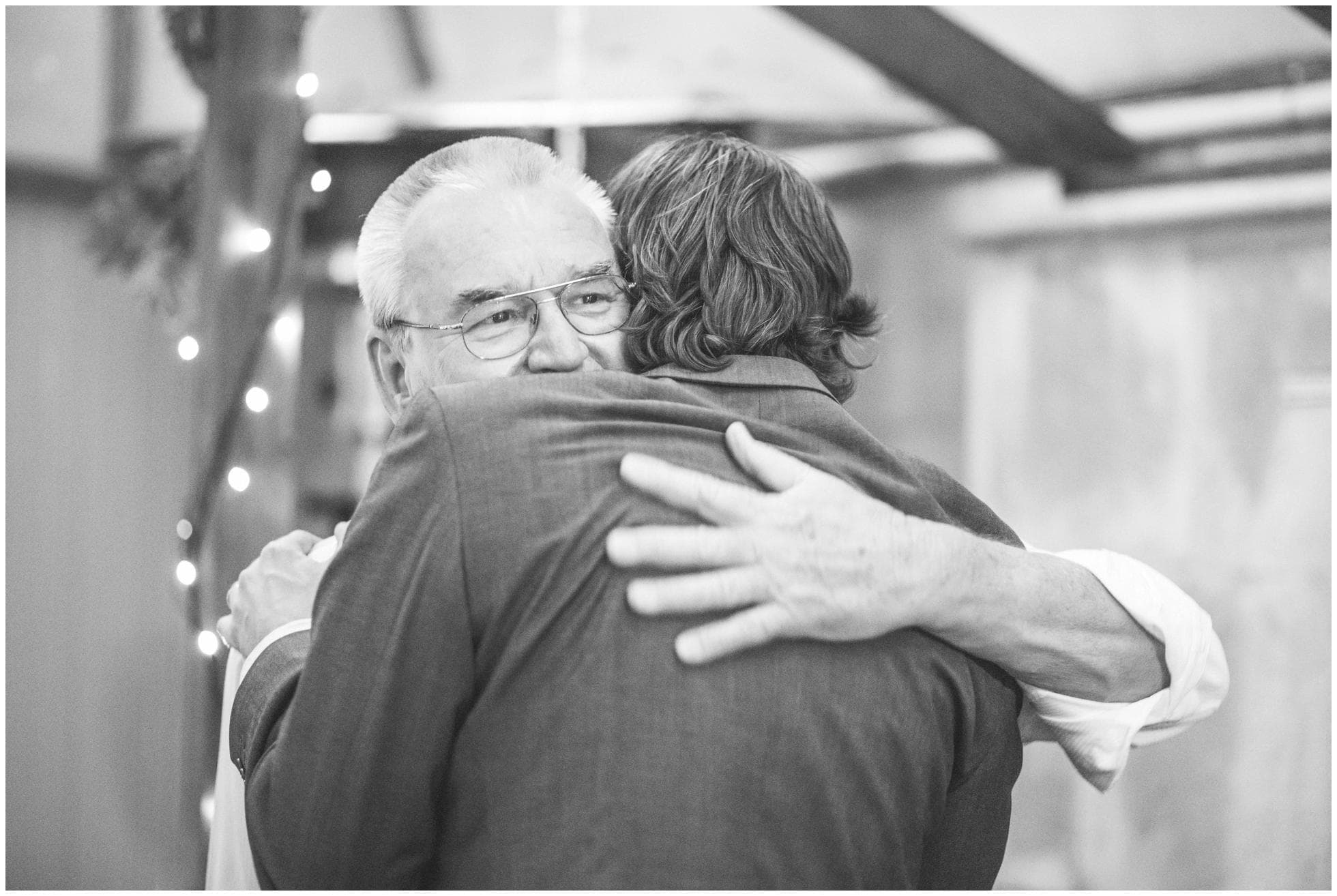 The father of the groom hugs his son after his speech