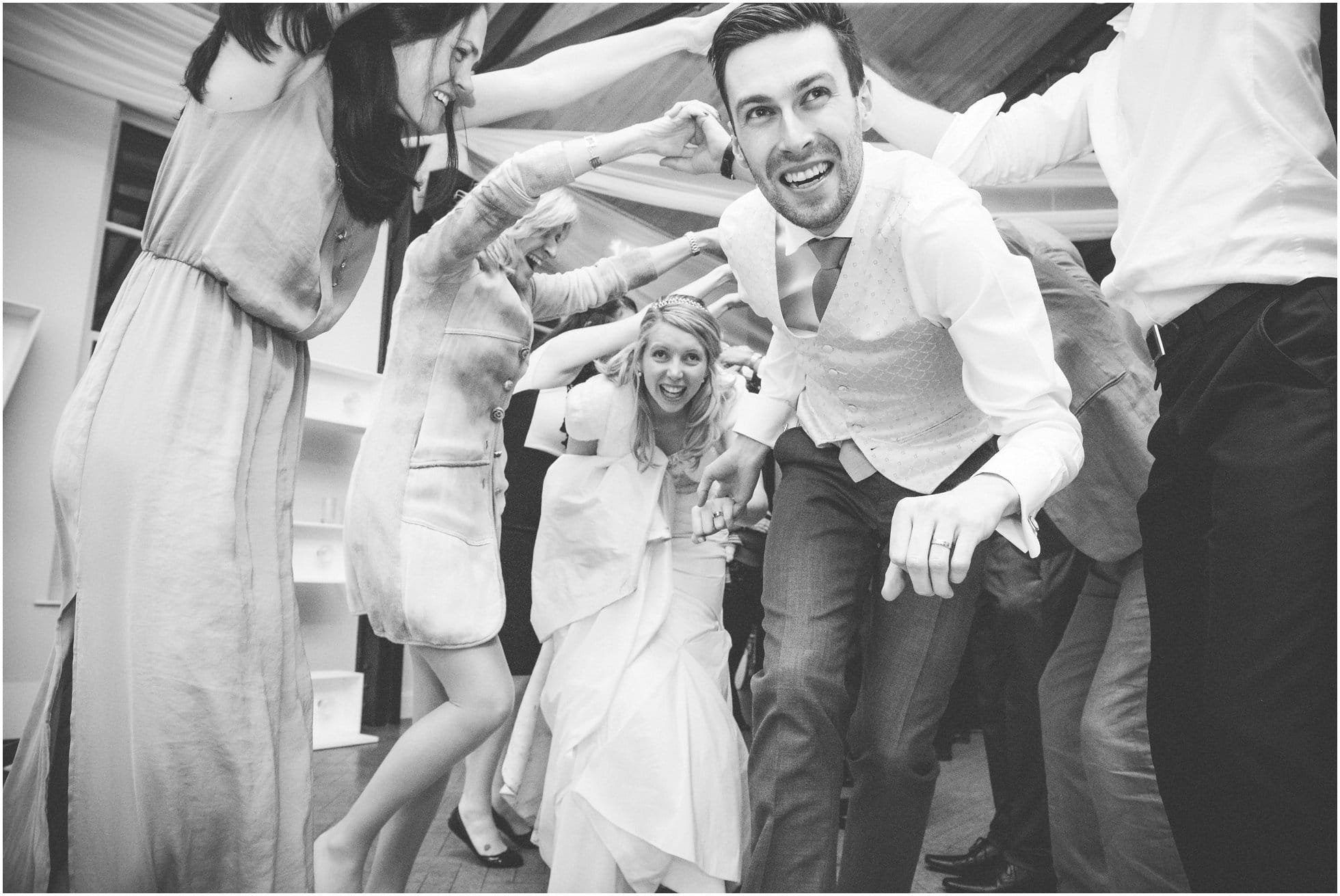 The bride and couple enjoying their wedding ceilidh at Brooksby Hall, Leicestershire: Fun photography!
