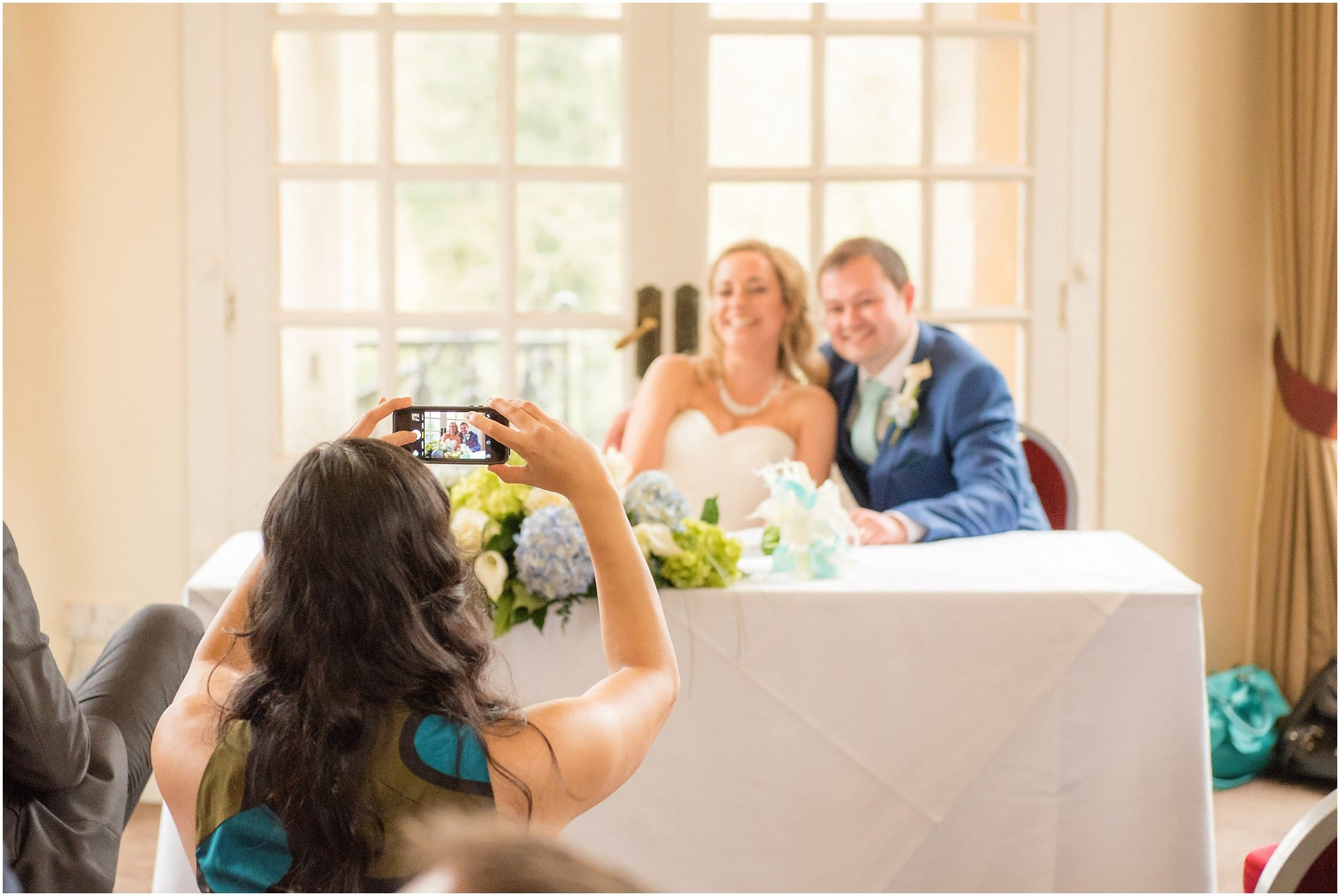 Guests photographing the bride and groom