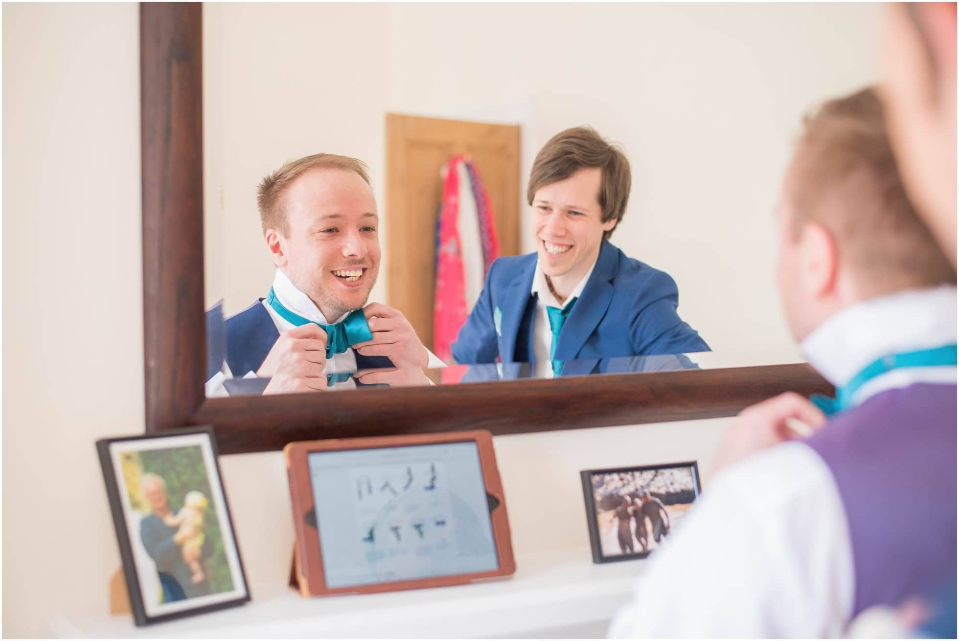 Groom and bestman trying to tie a bowtie in vain!