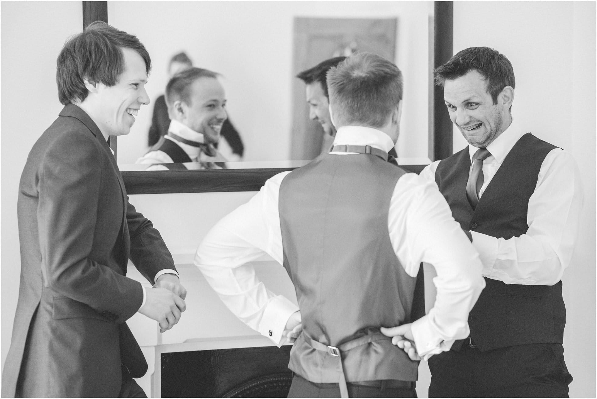 Groom and groomsmen trying to do up a bowtie
