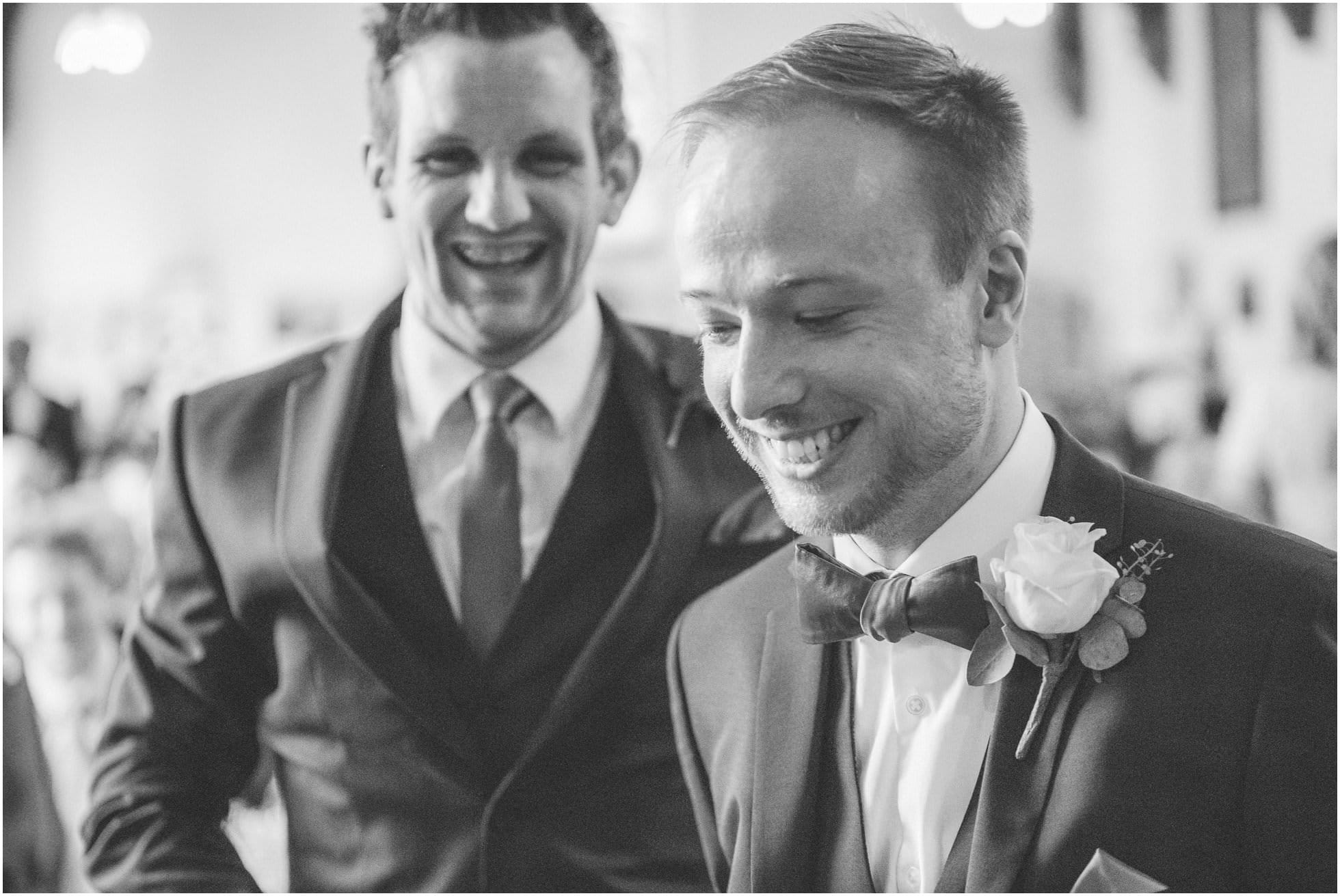 Unobtrusive wedding photography shot of groom and bestman