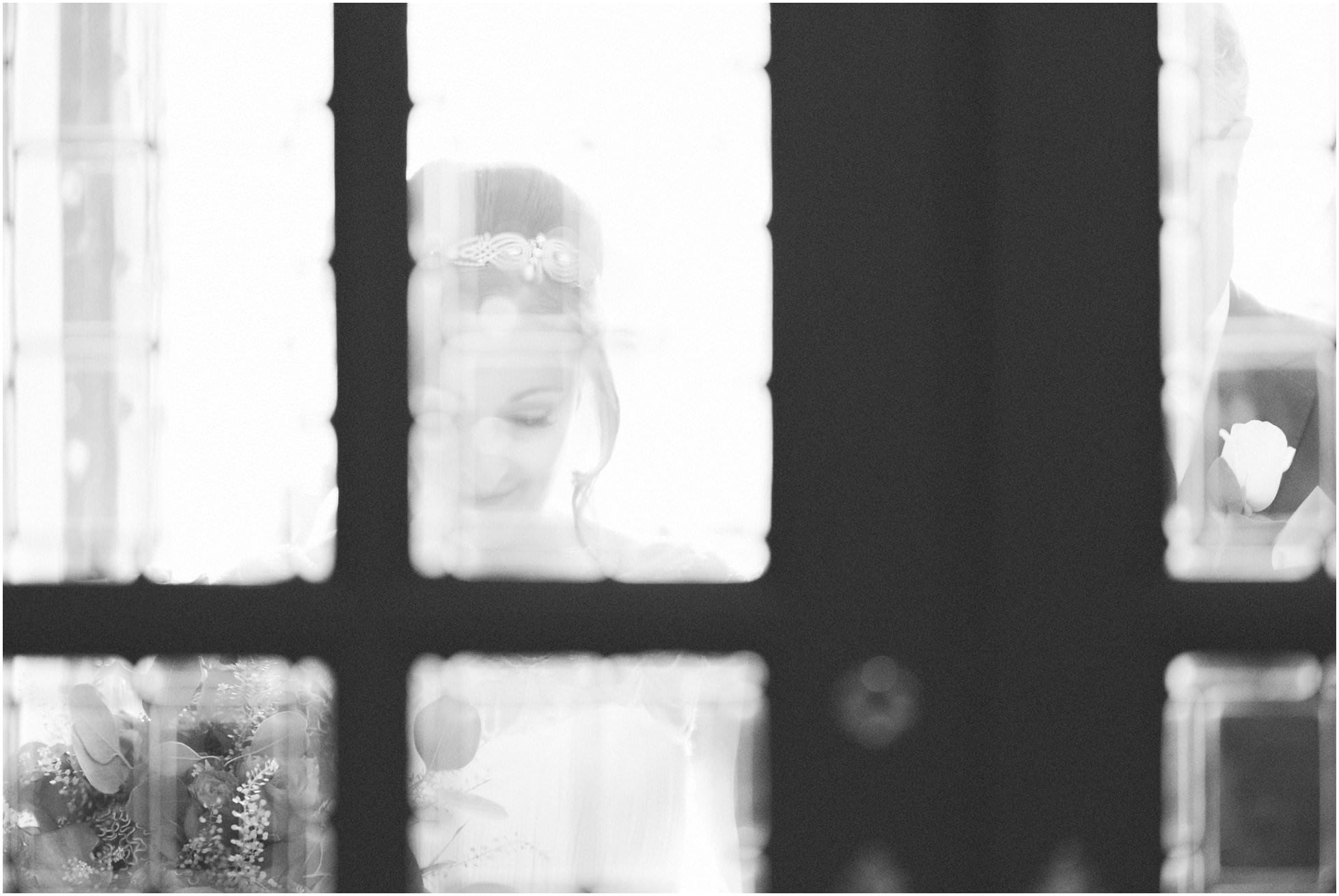 Bride through the glass of the church doors