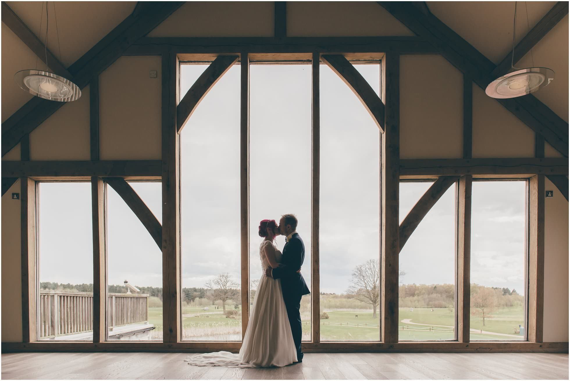 Gorgeous silhouette wedding shot in front of the big glass windows at Sandburn Hall