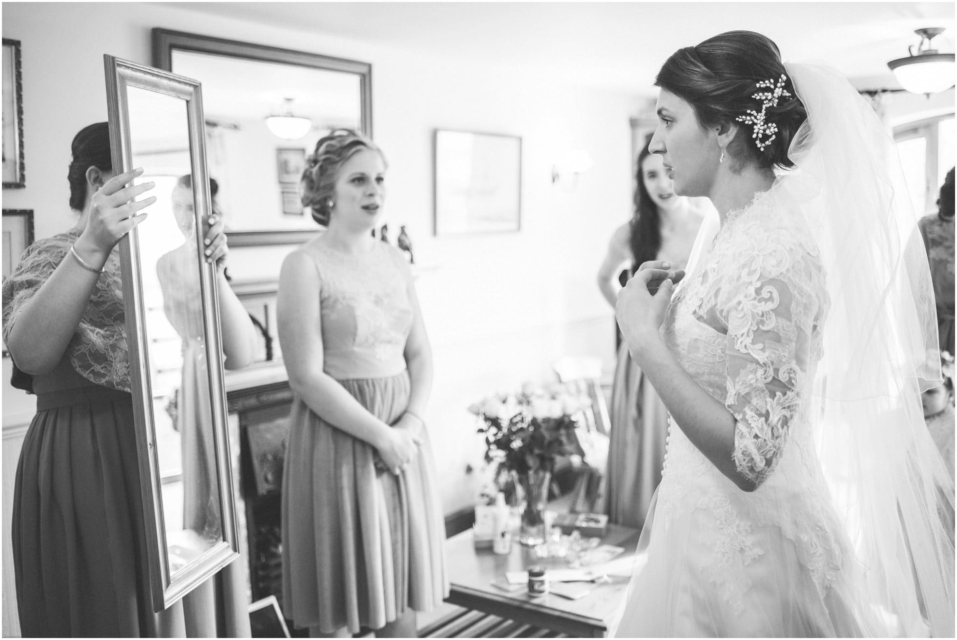 Bride looking into the mirror after putting dress on
