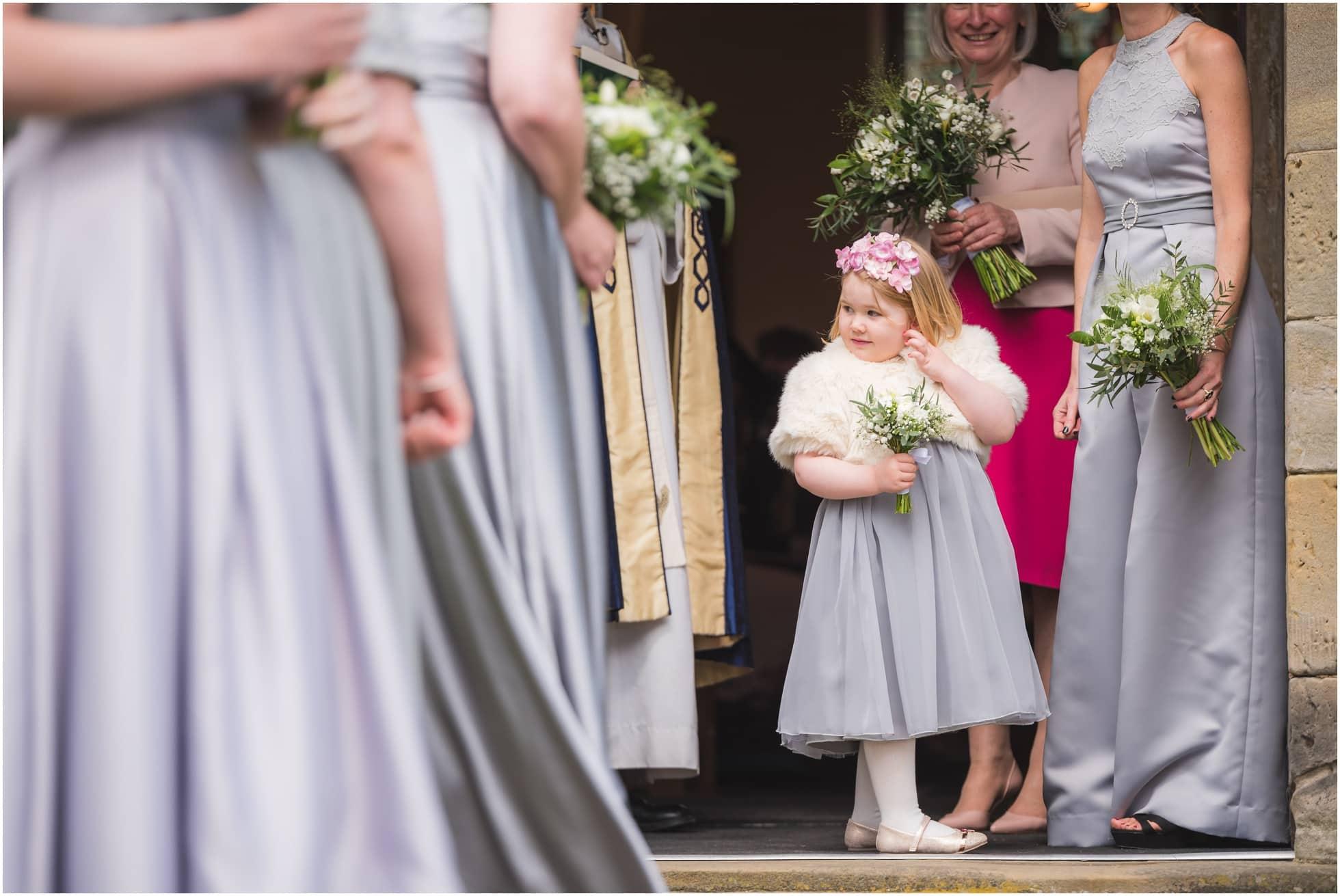 A little bridesmaid waiting to go inside the church