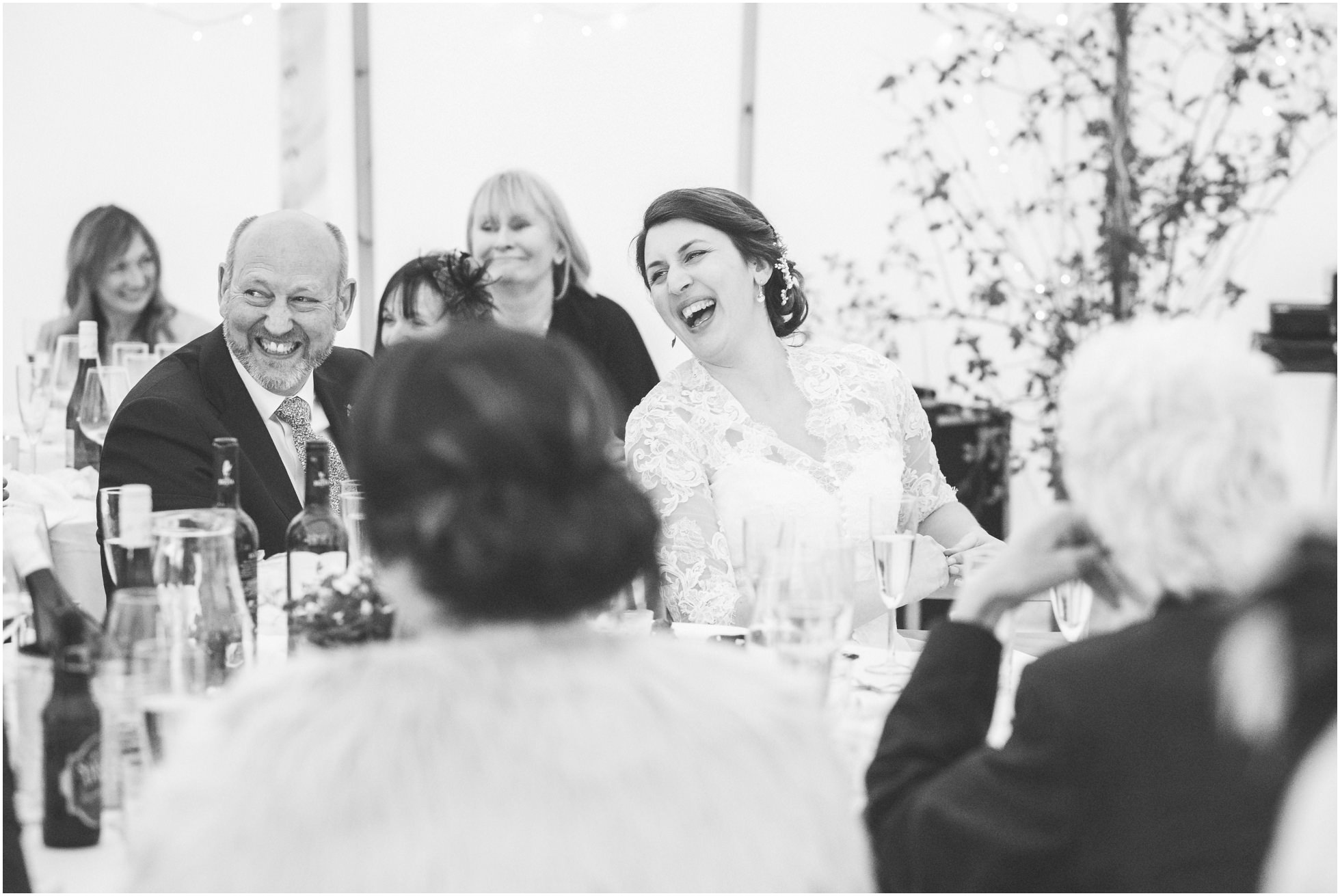 Bride and father laughing during the speeches