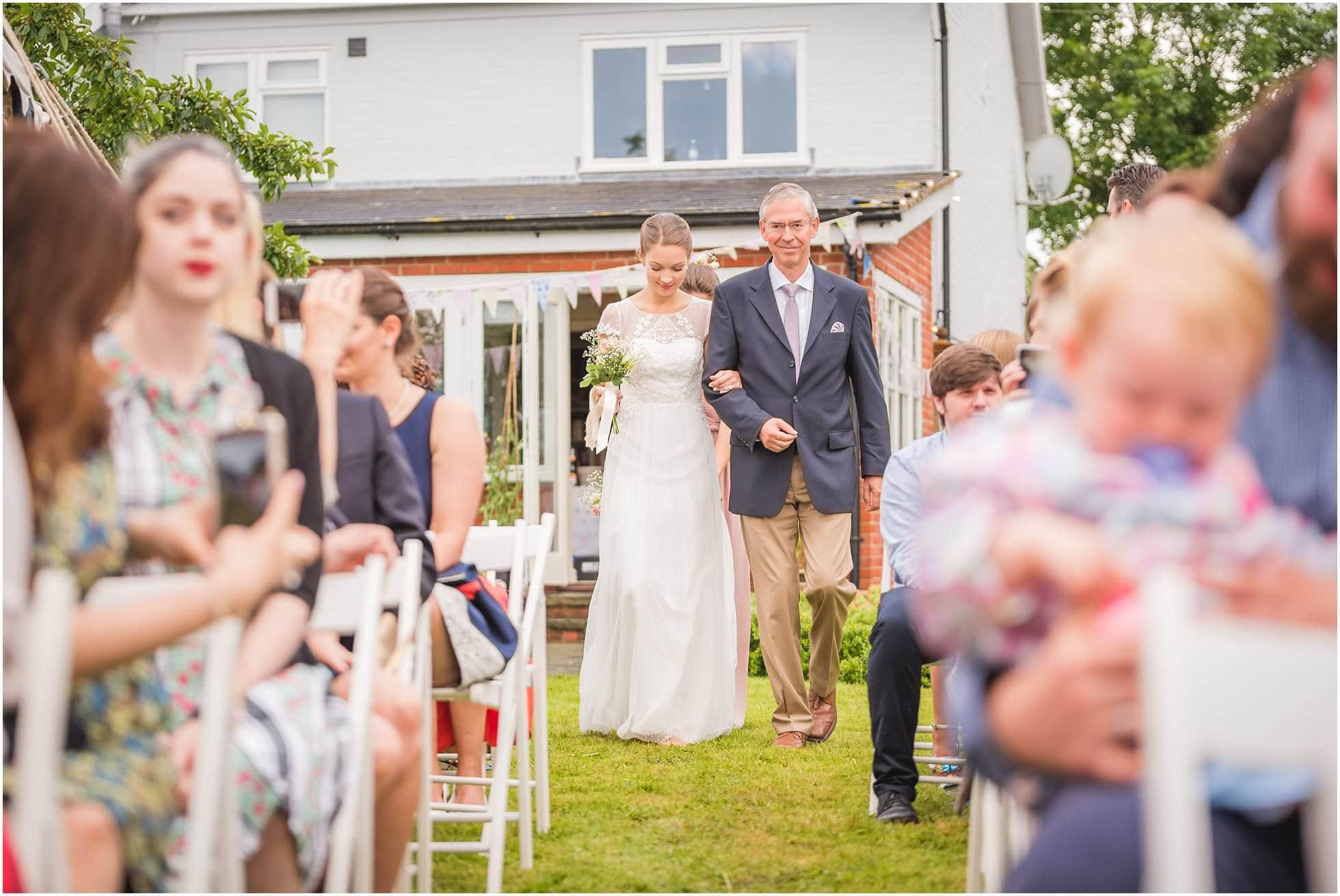 Here comes the bride at a Suffolk garden wedding