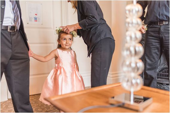 Cute flower girl has her flowers placed on her head at The Royal Horseguards Hotel