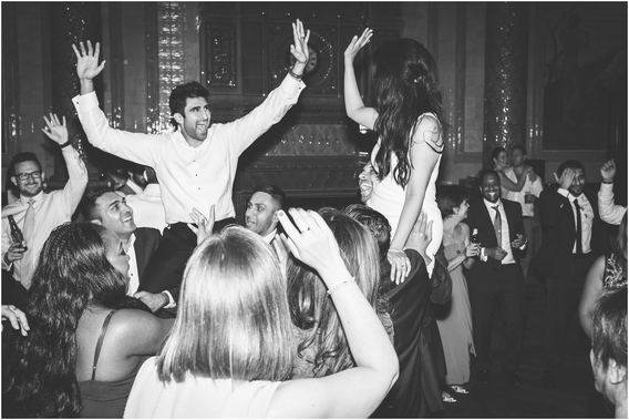 Bride and groom high five whilst being held up