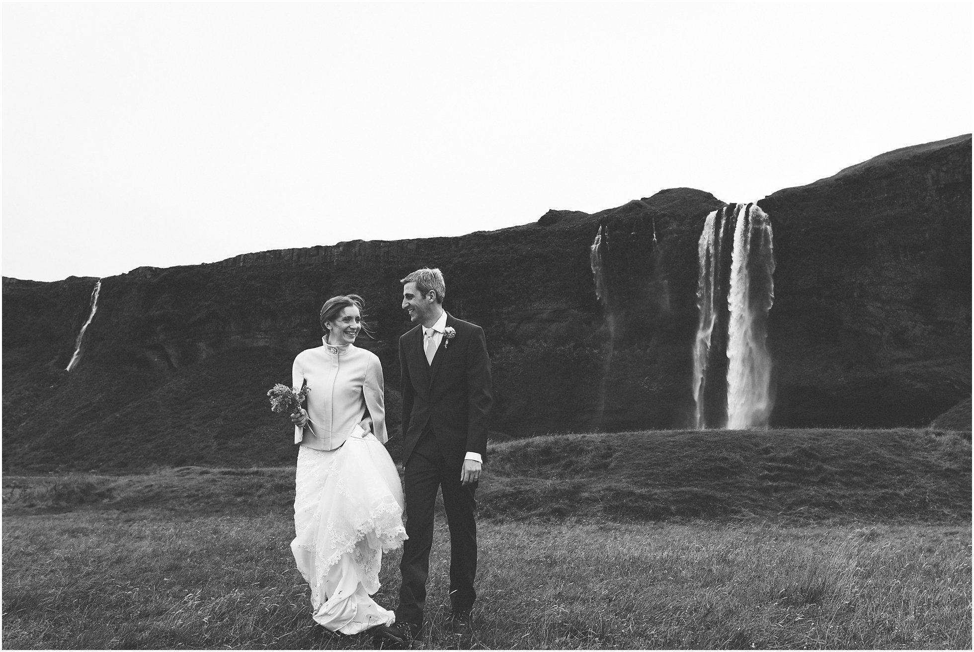 Bride and groom walking away from Seljalandsfoss