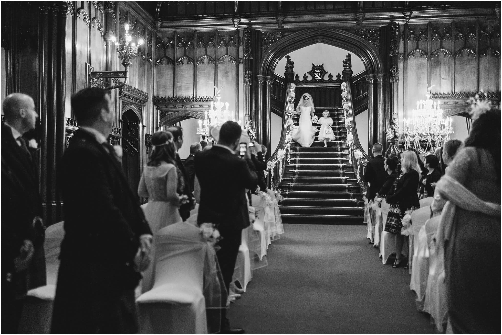 The bide and bridesmaid walk down the stairs of Allerton Castle