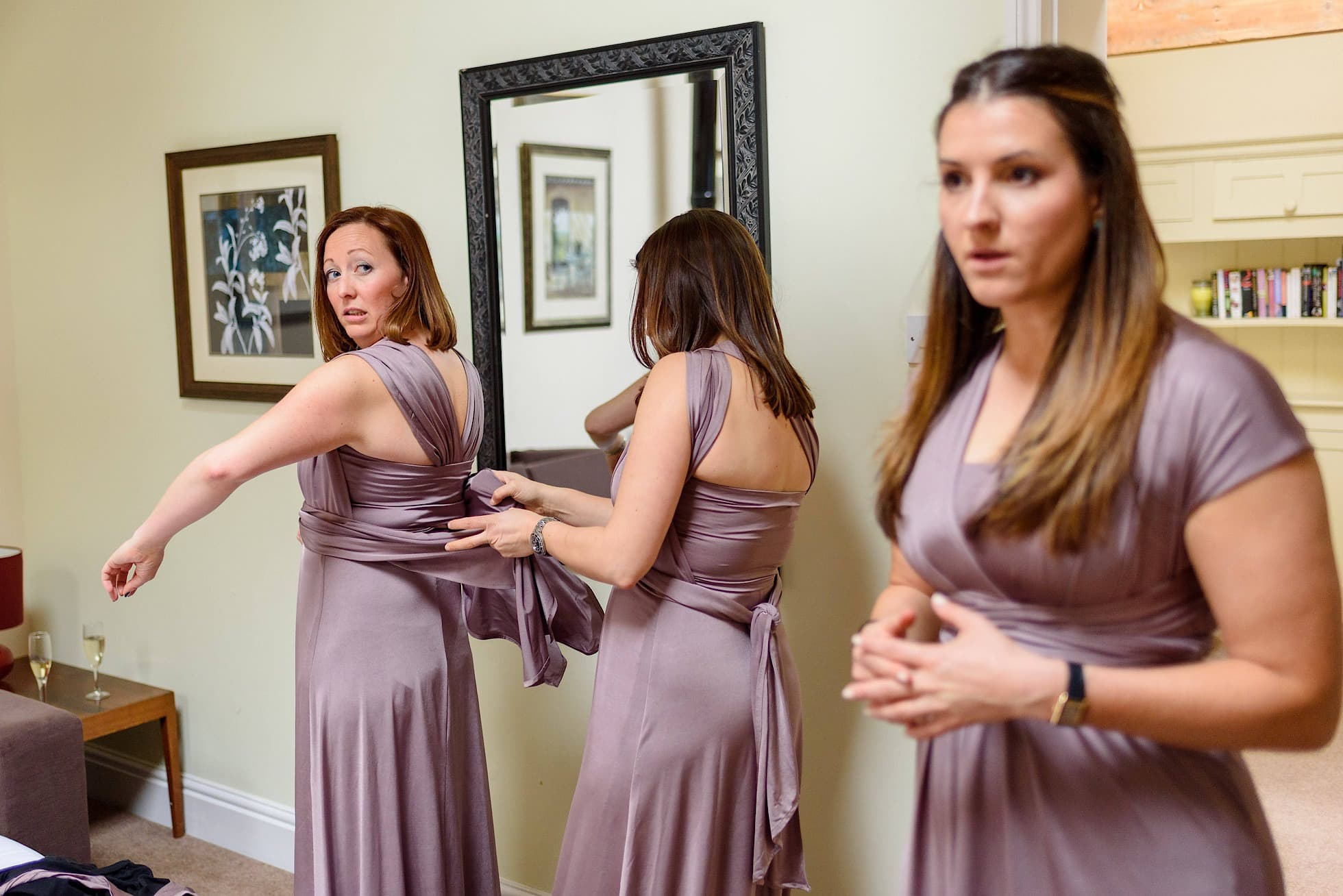 Bridesmaids struggling with the dresses