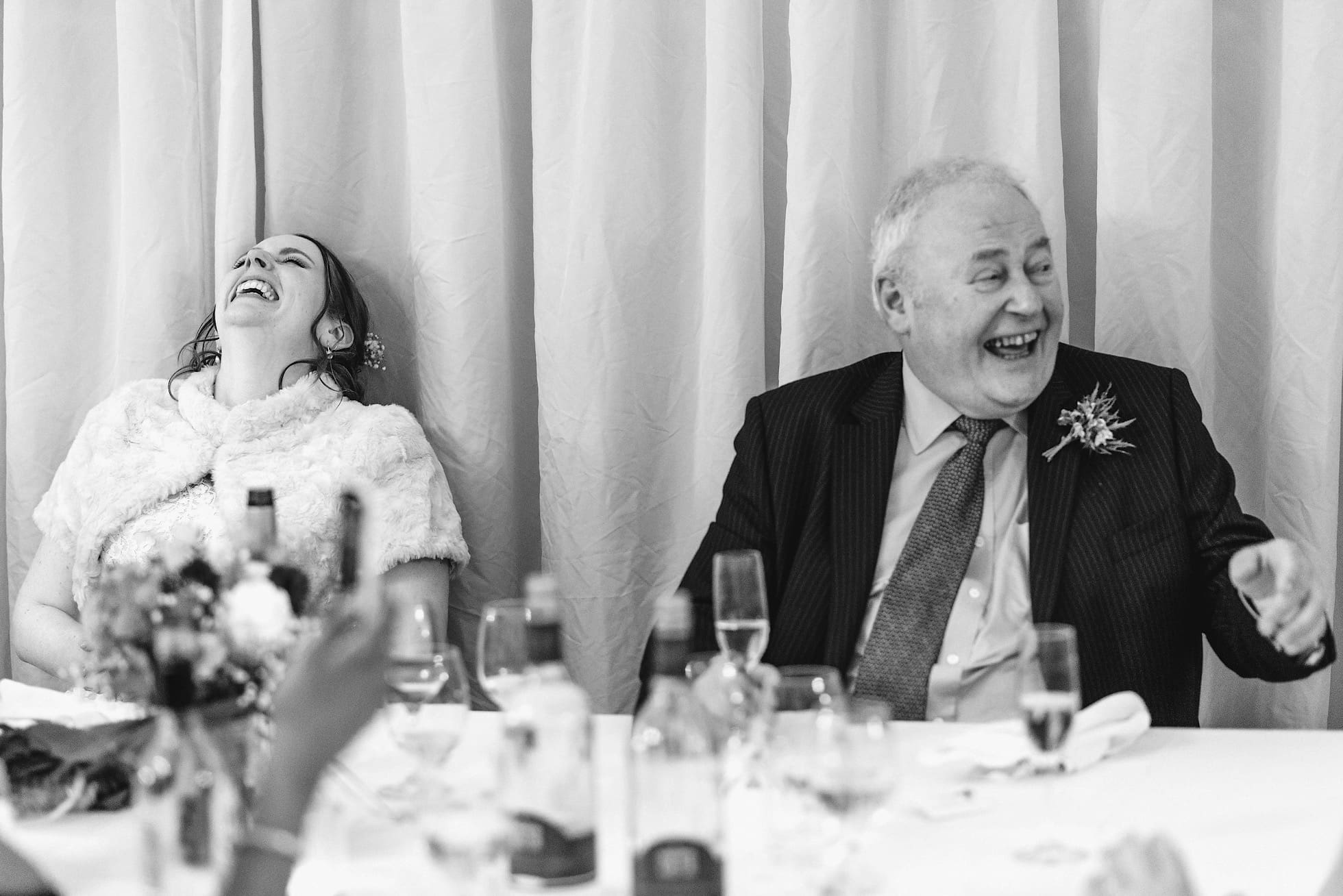 Bride and father of bride in tears of laughter