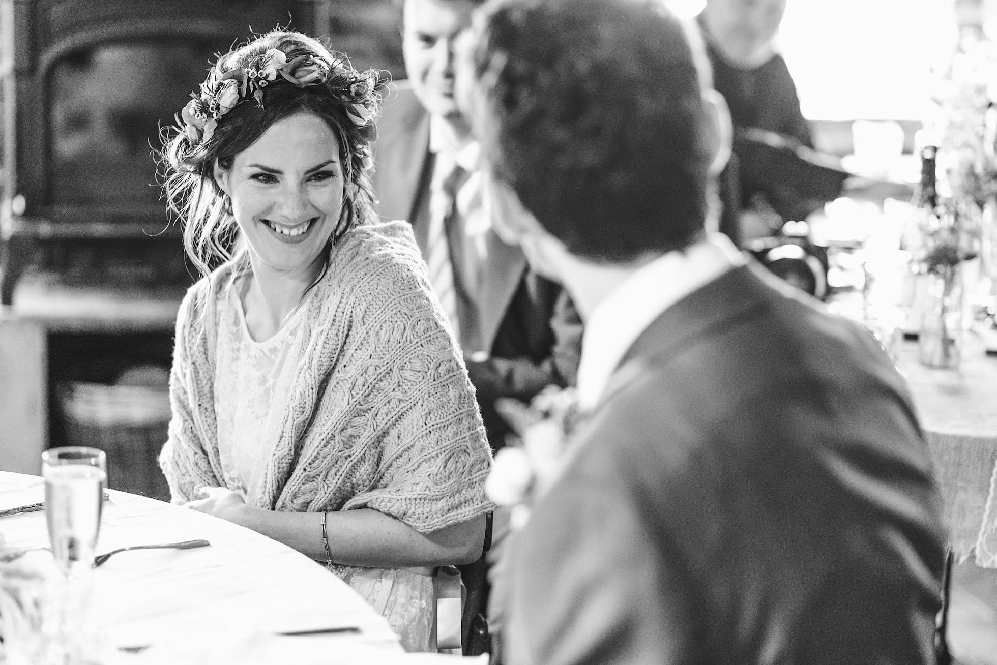 Bride smiles during the speeches, East Quay Venue Wedding Photographer