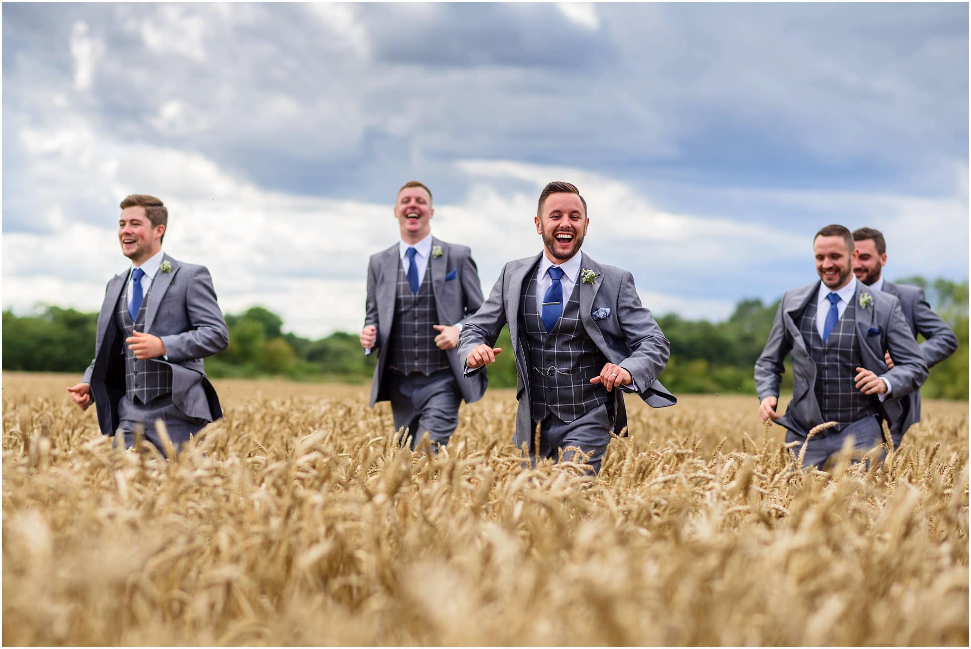 Groomsmen running in a wheat field