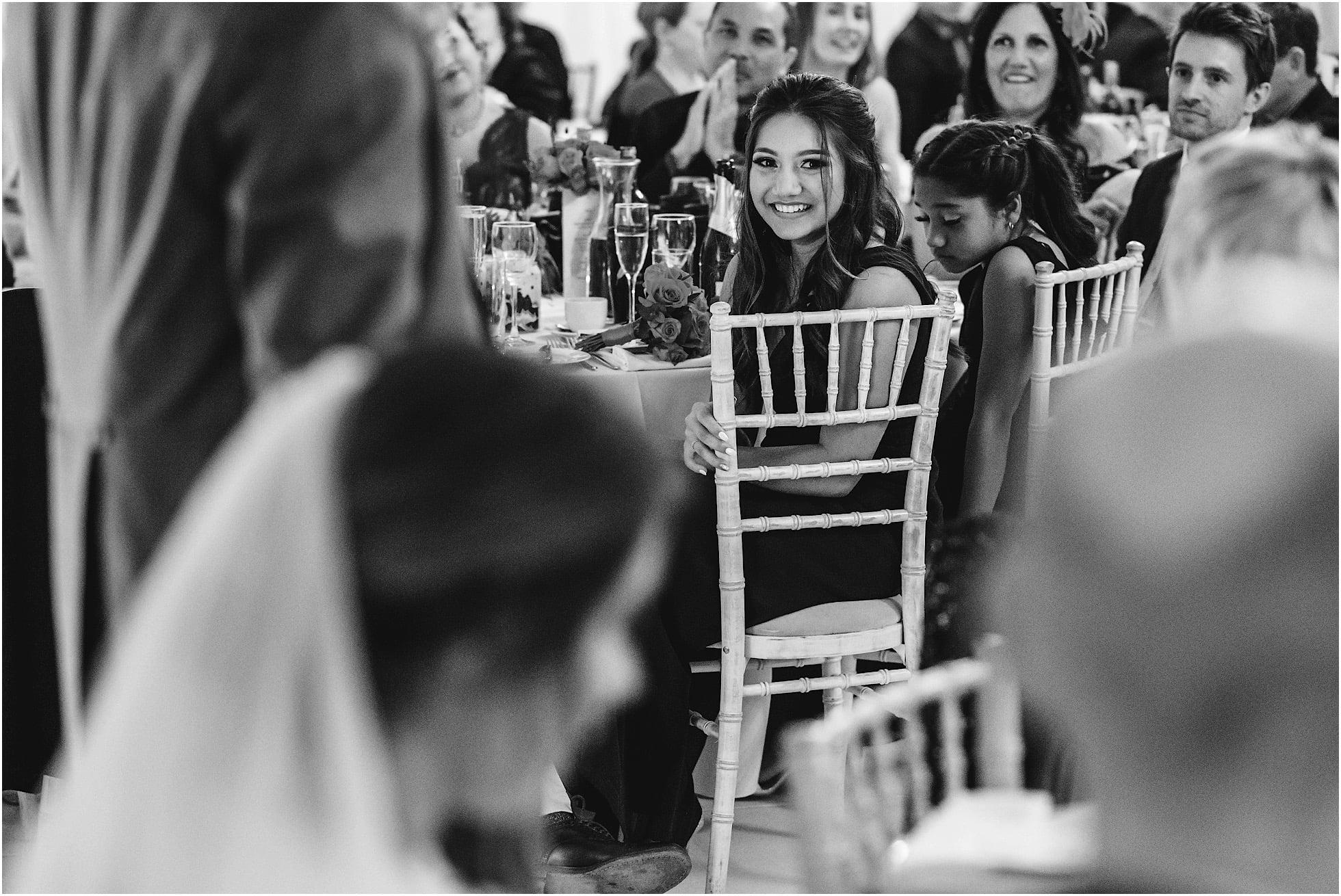 Bridesmaid smiles during speeches