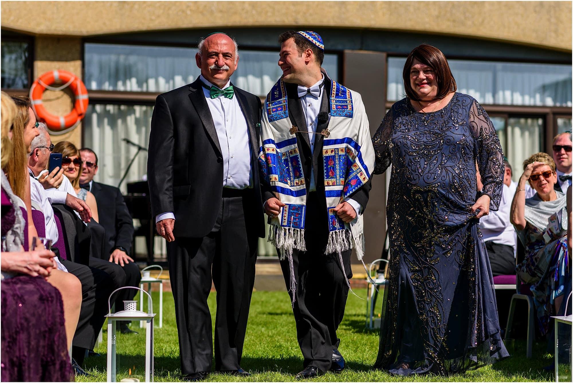 groom walks down aisle with parents jewish wedding
