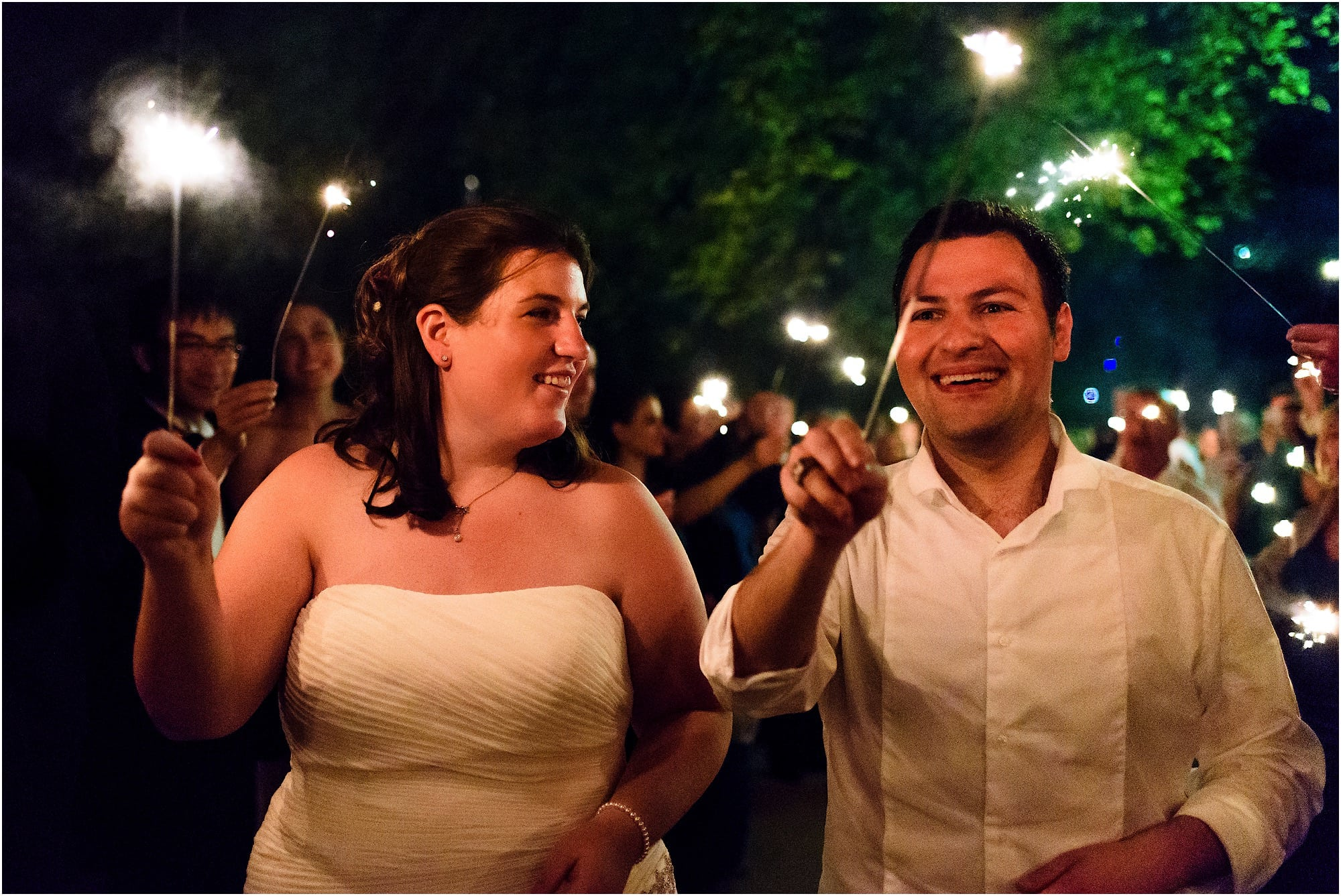 bride and groom with sparklers on the bridge
