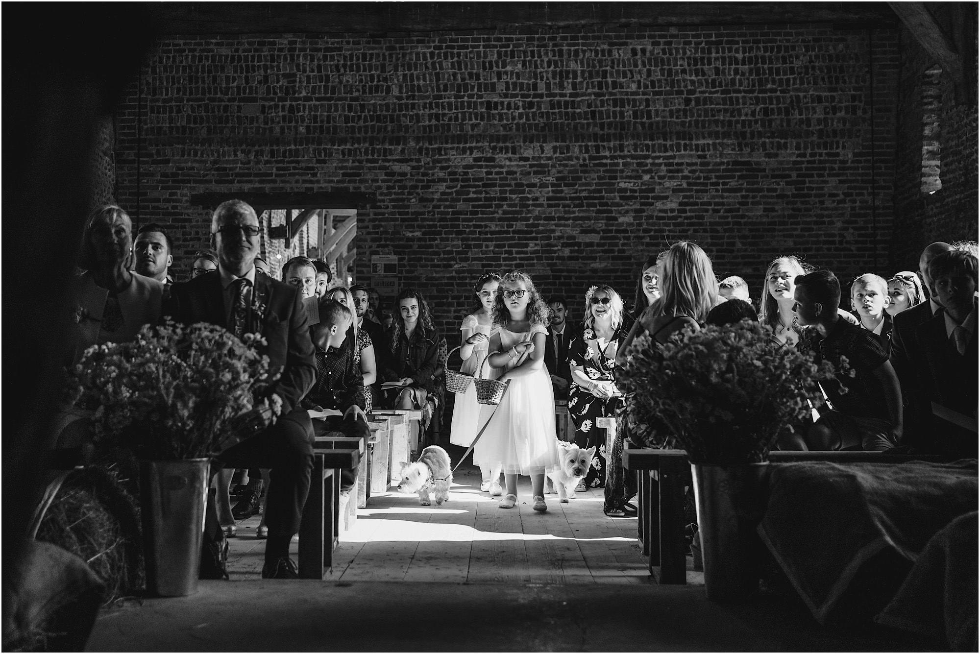 flower girls and Westies walking down the aisle at Waxham Barn