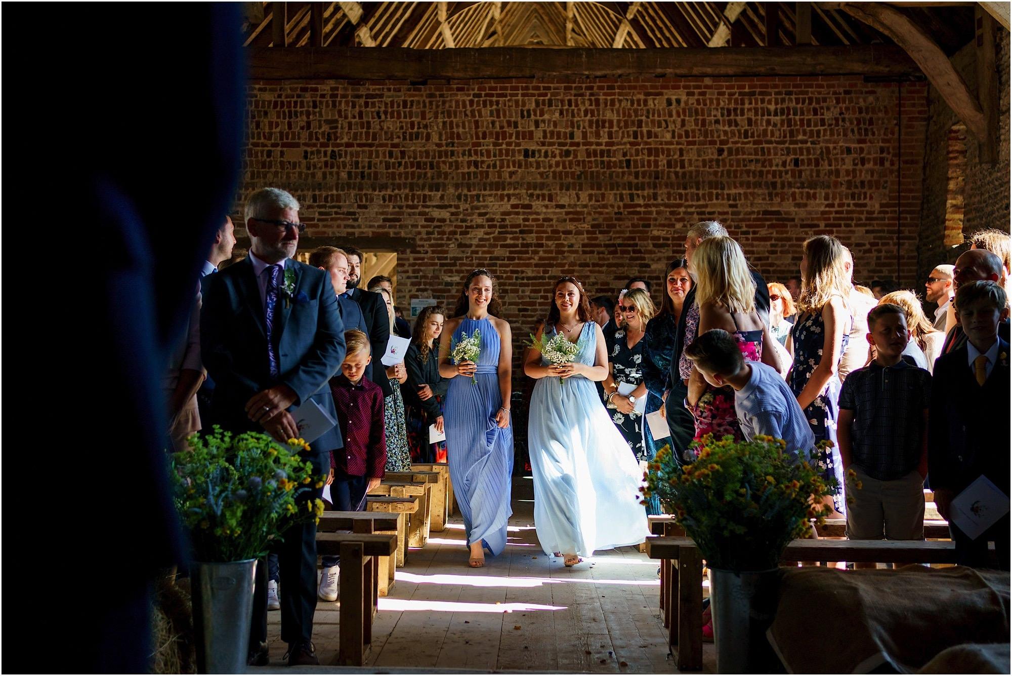 Bridesmaids walking down the aisle at Waxham Great Barn