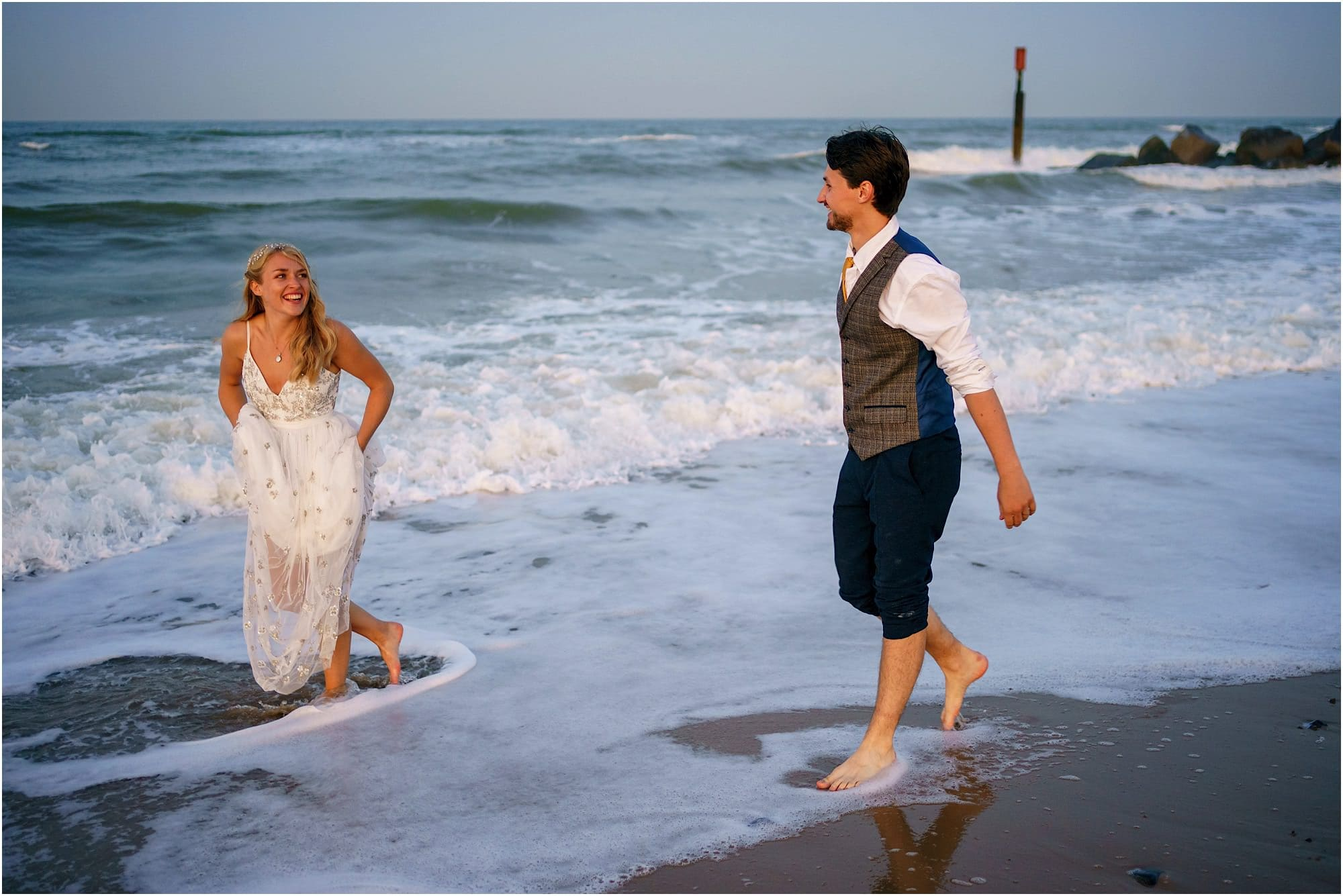 bride and groom paddling at Waxham beach