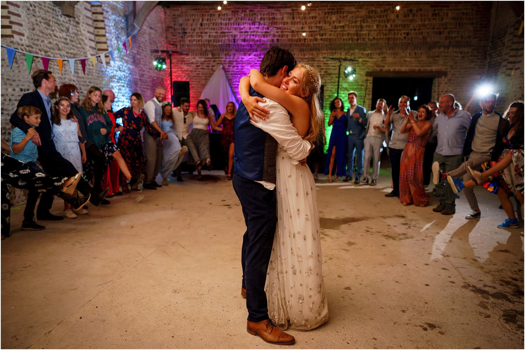 bride and groom in middle of a circle of guests dancing