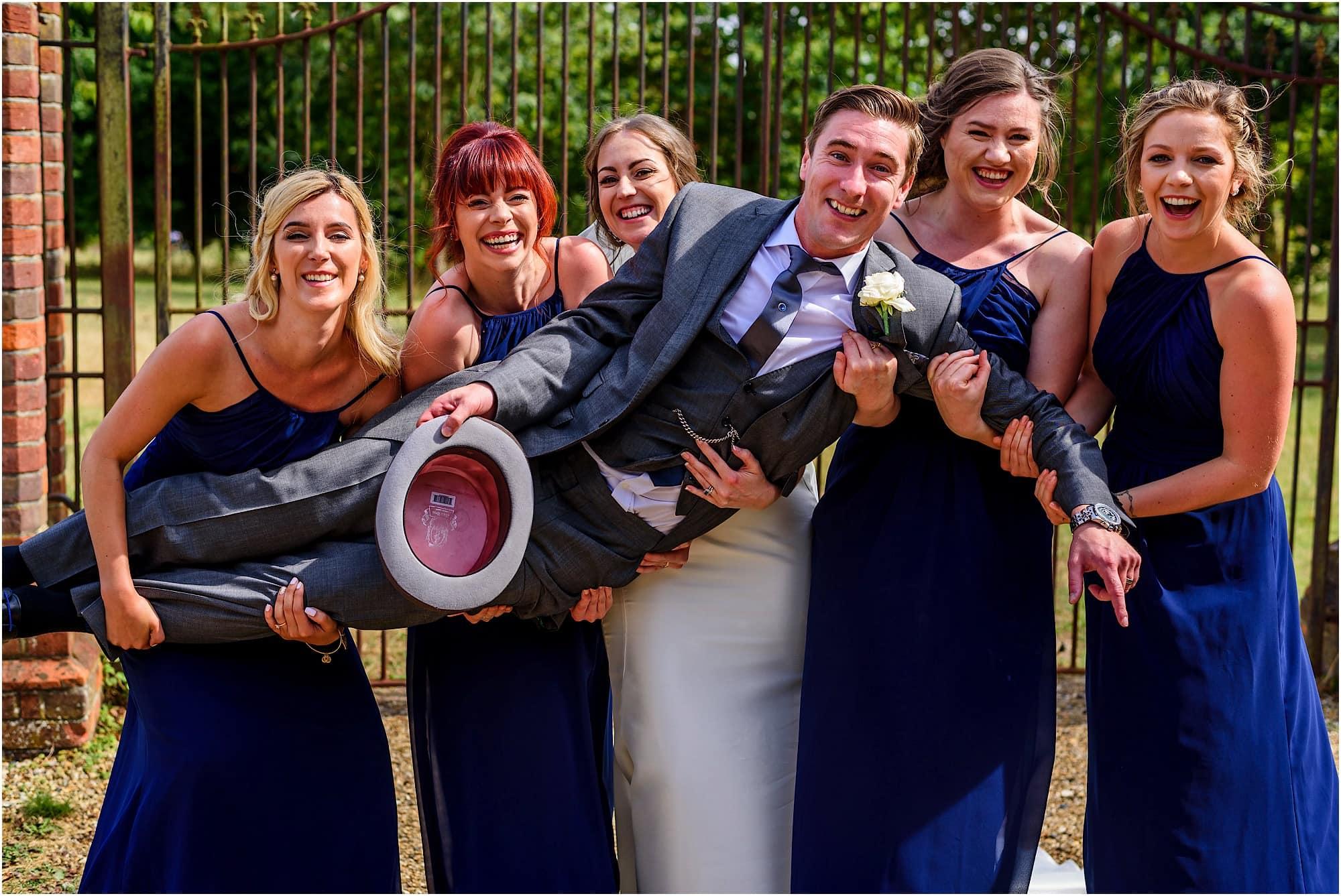 groom held by bridesmaids