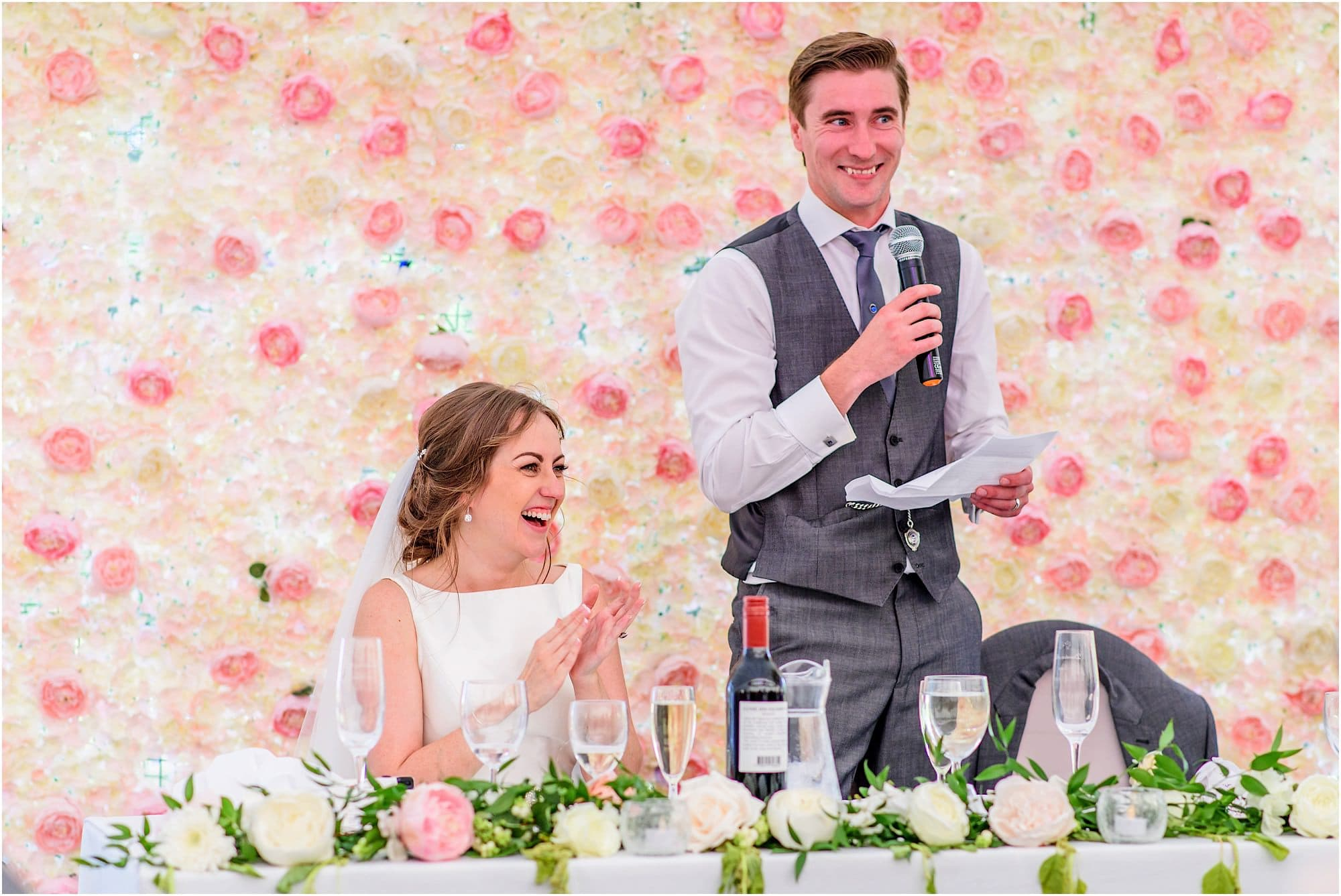 groom's speech in front of flower wall