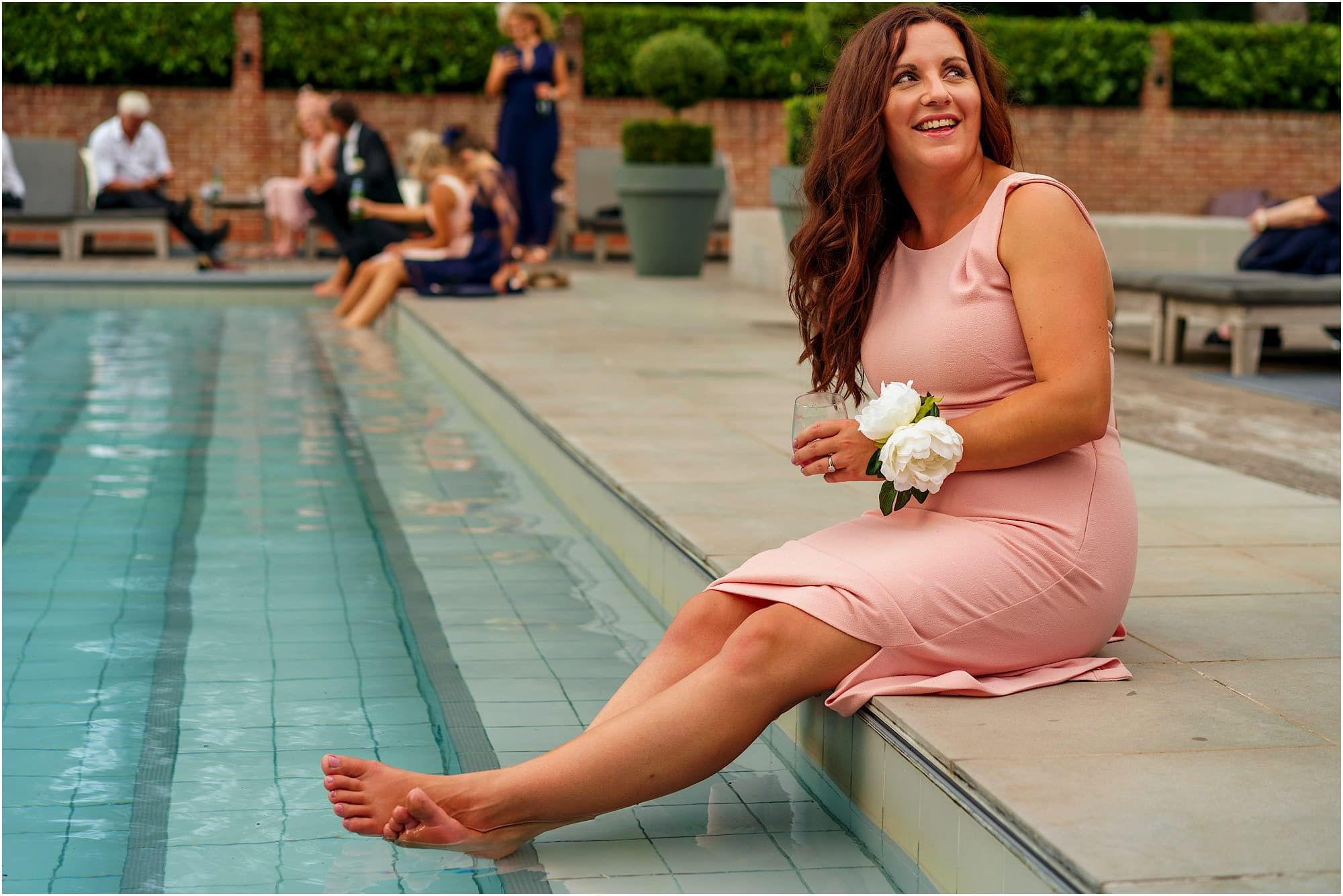bridesmaid dipping her feet in the pool